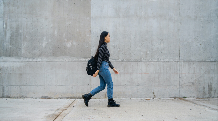 asian-woman-walking-against-grey-wall-UT8HZRY